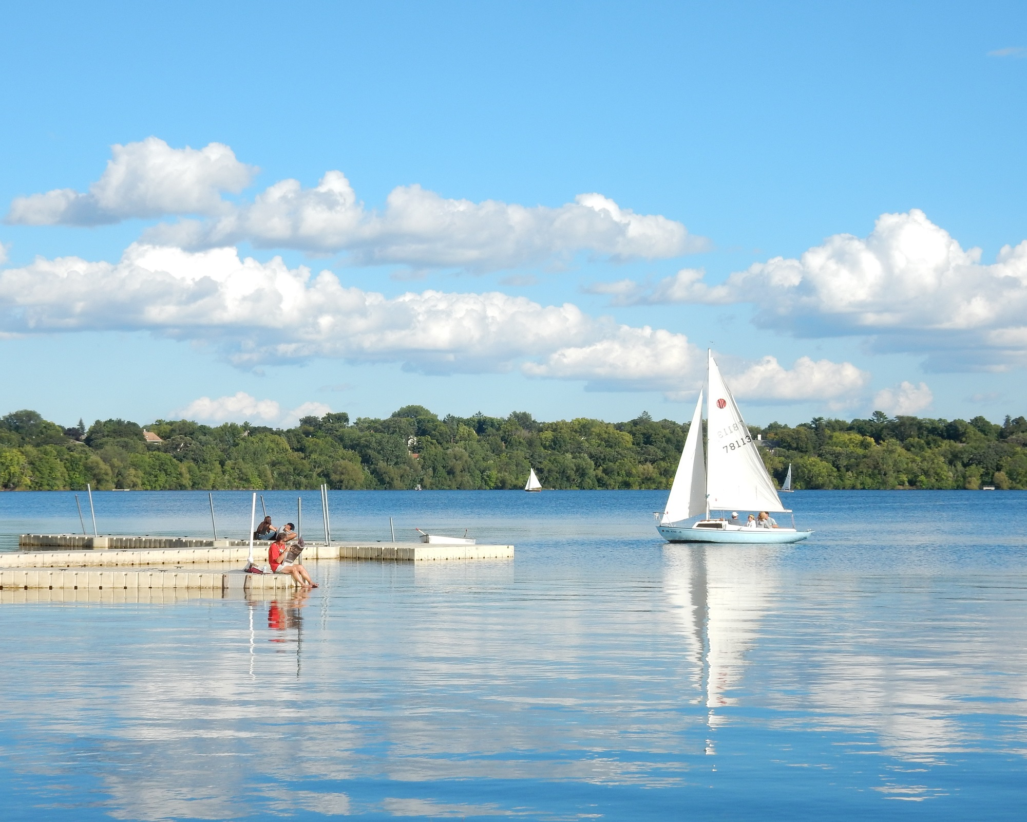 A sailboat and people on docks on Lake Harriet