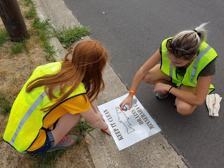 Teenage girls storm drain stenciling at the Greenway Cleanup