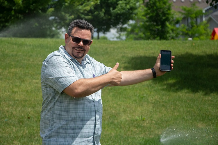 Man holding cellphone in front of lawn sprinklers