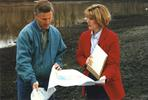 1990s Two people looking at Chain of Lakes Partnership plan
