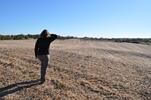 Person walking across tilled field