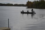3 people in a boating, netting fish