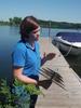 Kelly Dooley holding a zebra mussel plate on a dock