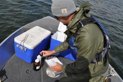 Person doing water quality sampling in a boat