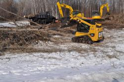 Construction equipment by brush piles